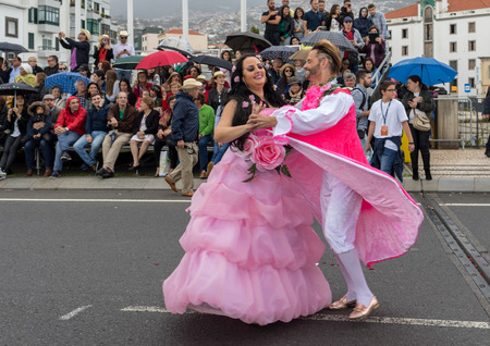 Funchal; Madeira; Portugal - April 22; 2018: A group of people in pink costumes are dancing at Madeira Flower Festival Parade in Funchal on the Island of Madeira. Portugal. Foto de archivo - 101774890