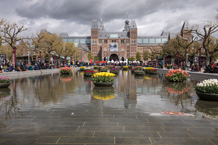 AMSTERDAM, NETHERLANDS - APRIL 22 2017: Rijksmuseum National Museum with I Amsterdam sign and tulips in the reflecting pool. Amsterdam, Netherlands Editorial