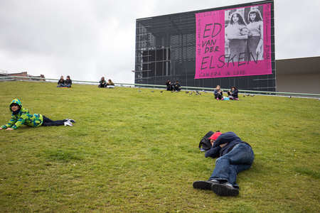 Amsterdam, Netherlands - April 22, 2017: Amsterdam Stedelijk Museum for modern, contemporary art and design. New annex seen from Museumplein, people resting on the grass. Netherlands