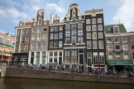 Amsterdam, Netherlands - April 20, 2017: Canal  scene with a bicycles and traditional Dutch houses in Red Light District. Amsterdam. Netherlands 에디토리얼
