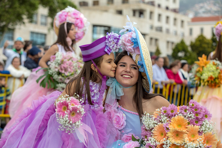 Funchal; Madeira; Portugal - April 22; 2018: Mom and her daughter  in colorful costumes at Madeira Flower Festival Parade in Funchal on the Island of Madeira. Portugal. Foto de archivo - 105427734