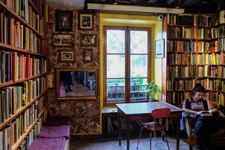 Paris, Frankreich - November 2017: Frau, die vor Regalen voller alter Bücher sitzt. Shakespeare & Company, Paris, Frankreich. Editorial