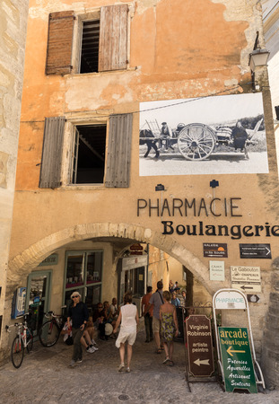 GORDES, FRANCE - JUNE 25, 2017: A typical old stone house with a billboard depicting the scenes of old-fashioned life in Gordes village, Vaucluse, Provence, France