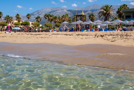 Malia, Crete, Greece - July 1, 2018: People are resting on a sunny day at the beach in Malia, Crete, Greece Editorial