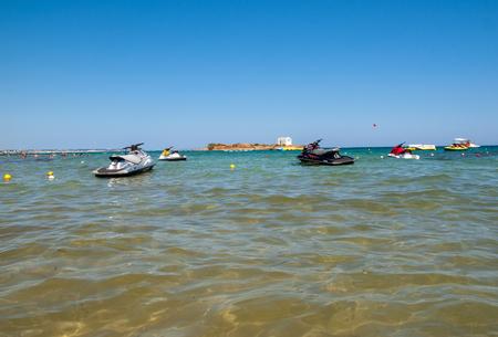 Malia, Crete, Greece - July 2, 2018: A view of a beach with a water scooters  in Malia. Crete, Greece