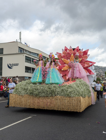 Funchal; Madeira; Portugal - April 22; 2018: Girls in colorful costumes on the floral float at Madeira Flower Festival Parade in Funchal on the Island of Madeira. Portugal. Foto de archivo - 107182024
