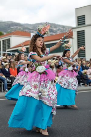 Funchal; Madeira; Portugal - April 22; 2018: A group of girls in colorful costumes are dancing at Madeira Flower Festival Parade in Funchal on the Island of Madeira. Portugal. Foto de archivo - 107182064