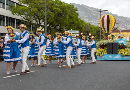 Funchal; Madeira; Portugal - April 22; 2018: A group of people in colorful costumes are dancing at Madeira Flower Festival Parade in Funchal on the Island of Madeira. Portugal. 報道画像