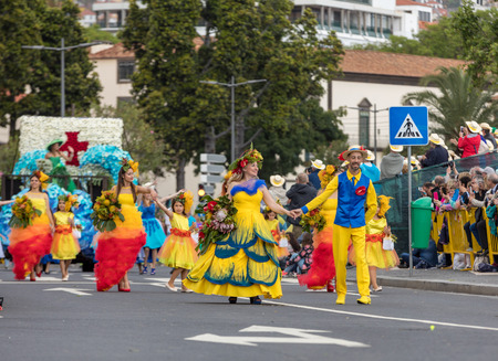 Funchal; Madeira; Portugal - April 22; 2018: A group of people in colorful costumes are dancing at Madeira Flower Festival Parade in Funchal on the Island of Madeira. Portugal. Foto de archivo - 108846960