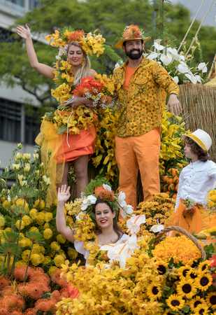 Funchal; Madeira; Portugal - April 22; 2018: A group of people in colorful costumes on the floral float at Madeira Flower Festival Parade in Funchal on the Island of Madeira. Portugal. Foto de archivo - 108846975