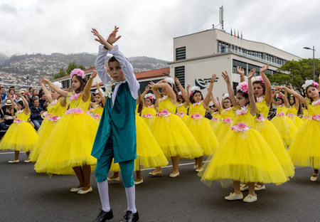 Funchal; Madeira; Portugal - April 22; 2018: A group of girls in colorful costumes are dancing at Madeira Flower Festival Parade in Funchal on the Island of Madeira. Portugal. Foto de archivo - 109123482