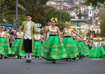 Funchal; Madeira; Portugal - April 22; 2018: a group of people  in colorful dresses with sunflowers motifs are dancing at Madeira Flower Festival Parade in Funchal on the Island of Madeira. Portugal. Foto de archivo - 109123456