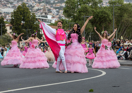 Funchal; Madeira; Portugal - April 22; 2018: A group of people in pink costumes are dancing at Madeira Flower Festival Parade in Funchal on the Island of Madeira. Portugal. Foto de archivo - 109123461