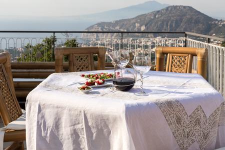 Preparado para la mesa de la cena en la terraza con vistas a la bahía de Nápoles y al Vesubio. Sorrento. Italia