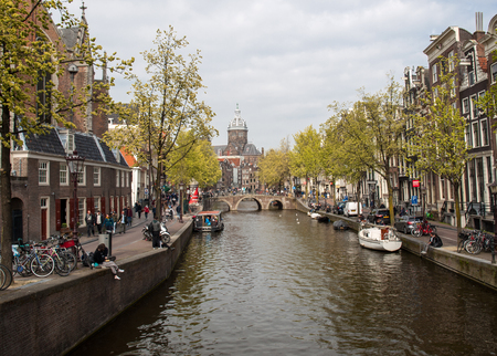 Amsterdam, Netherlands - April 20, 2017: Canal  scene with a bicycles, boats and traditional Dutch houses in Red Light District. Amsterdam. Netherlands