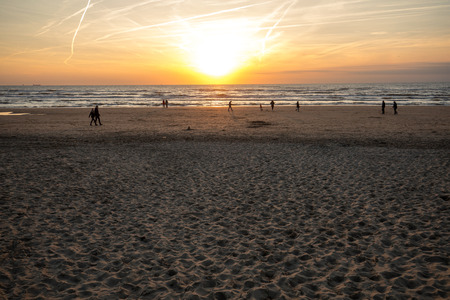 Katwijk, Netherlands - April 23, 2017: People are walking along the beach in Katwijk at sunset. Netherlands Editorial