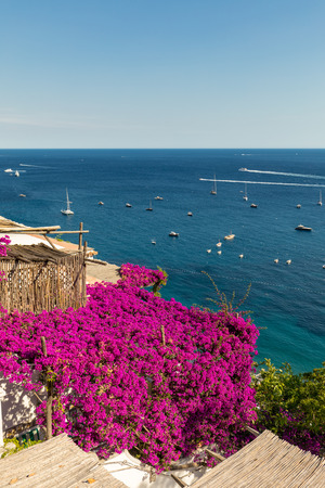 Positano framed by pink bougainvillea and boats in the background. Colourful Positano, the jewel of the Amalfi Coast, with its multicoloured homes and buildings perched on a large hill overlooking the sea. Italy Banque d'images