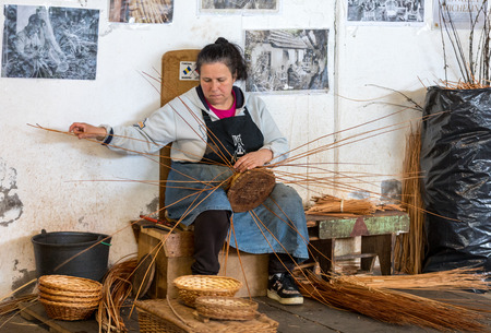 Camacha, Madeira, Portugal - April 19, 2018: A basket weaver at work in the factory shop in Camacha on Madeira Island, Portugal