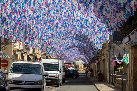 Saint Cyprien, France - September 4, 2018: Colourful street decorations during the summer Felibree in Saint Cyprien, France. A felibree is a traditional Occitan festival which takes place every year in a town or village in the Dordogne. 写真素材 - 114871158