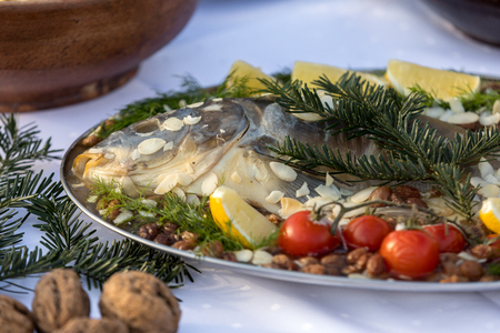 carp with lemon, almonds and cherry tomatoes on the plate Reklamní fotografie