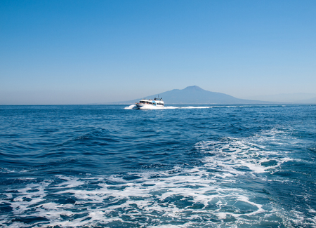 Sorrento, Italy - June 13, 2017: Cruise Boat in front of Mount Vesuvius in Bay of Naples at Sorrento resort town. Italy