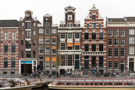 Amsterdam, Netherlands - April 20, 2017: View on Rokin Canal, Oude Turfmarkt street and Tourboats ready for canal cruises in Amsterdam, Holland, Netherlands.