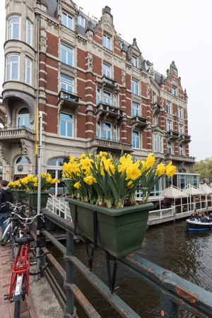 Amsterdam, Netherlands - April 20, 2017: Canal  scene with a bicycles and traditional Dutch houses in Amsterdam. Netherlands
