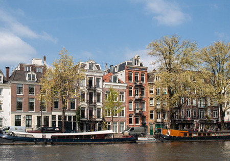 Amsterdam, Netherlands - April 20, 2017: Traditional historic Dutch gable houses beside canal in Amsterdam The Netherlands