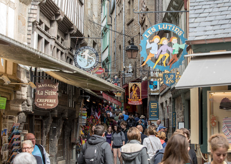 Le Mont-Saint-Michel, France - September 13, 2018: A crowd of tourists on Grand Rue, the main street in Mont Saint Michele. Normandy, France