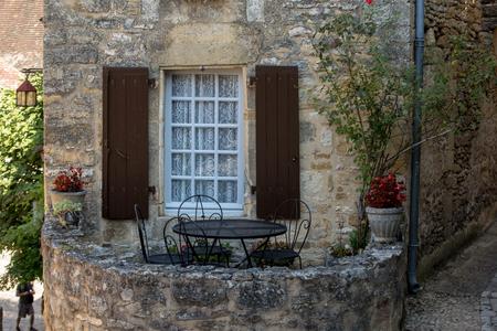 Ein schwarzer Metalltisch und Stühle auf der romantischen Terrasse eines alten Steinhauses in Beynac-et-Cazenac, Frankreich
