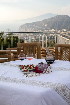 Table on the terrace prepared for a romantic dinner overlooking the Gulf of Naples and Mount Vesuvius Фото со стока