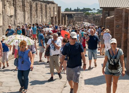 Pompeii, Italy - June 15, 2017:  The famous archaeological site of Pompeii. The crowd of tourists under the scorching sun. 스톡 콘텐츠