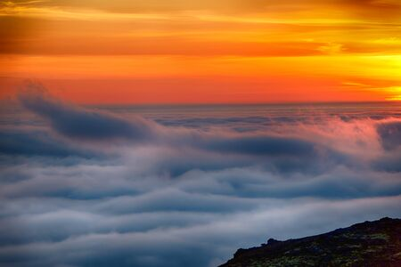 Dreamy misty landscape above the sea of clouds, mountains at sunset in Iceland