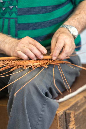 A basket weaver at work in the factory shop in Camacha on Madeira Island, Portugal