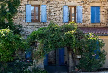 Facade of an old stone house with wooden shutters in Carlux. Dordogne valley, Aquitaine,  France Foto de archivo - 129241323