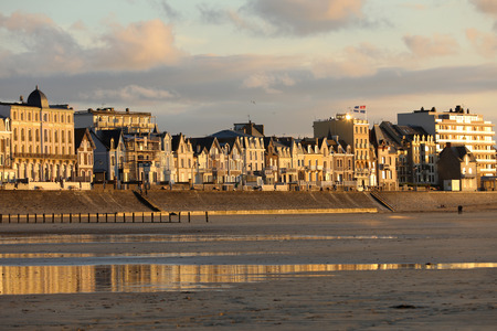 St Malo, France - September 14, 2018: Beach in the evening sun and buildings along the seafront promenade in Saint Malo. Brittany, France