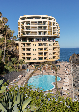 Funchal, Madeira, Portugal - April 17, 2018:  Swimming pool with tourists at Lido hotels zone in Funchal, Madeira island, Portugal