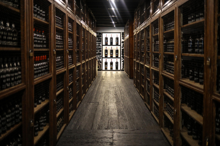 Funchal, Madeira, Portugal - April 23, 2018: Museum - repository of expensive vintage wine Madera. Long rows of shelves made of bottles of wine. funchal, Madera. Portugal 스톡 콘텐츠 - 124999267