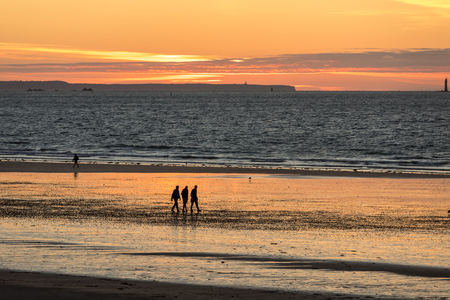 St Malo, France - September 14, 2018: Romantic walk of people before sunset on the picturesque beach of Saint Malo. Brittany, France