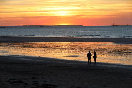 St Malo, France - September 15, 2018: Romantic walk of people before sunset on the picturesque beach of Saint Malo. Brittany, France