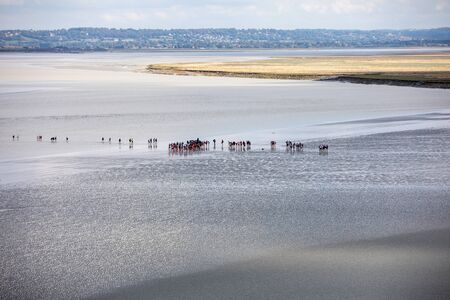 Le Mont-Saint-Michel, France - September 13, 2018: Group of hikers in the bay at low tide. Hike in the bay with a knowledgeable guide. Mont Saint-Michel , Normandy, France Stockfoto