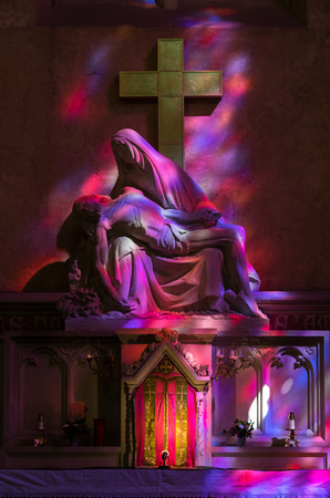 St Emilion, France - September 8, 2018: Pieta in Hues of Purple and red - symbolic reference to the color of the wine in the Collegiale church of St Emilion, France