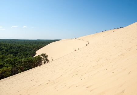 Dune of Pilat, France - September 10,2018: People walking on the top of the Dune of Pilat, the tallest sand dune in Europe. La Teste-de-Buch, Arcachon Bay, Aquitaine, France Фото со стока