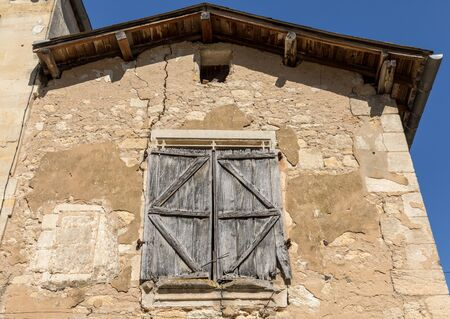 Front wall of an old stone house in Saint Emilion. France.  St Emilion is one of the principal red wine areas of Bordeaux and very popular tourist destination.