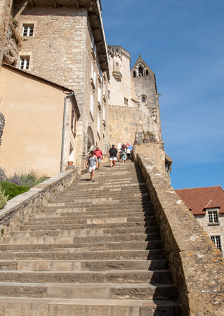 Rocamadour, France - September 3, 2018: People on steep steps Big stairs at Pilgrimage town of Rocamadour, Episcopal city and sanctuary of the Blessed Virgin Mary, Lot, Midi-Pyrenees, France Editöryel