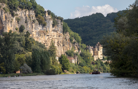 La Roque-Gageac, Dordogne, France - September 7, 2018: Canoeing and tourist boat, in French called gabare, on the river Dordogne at La Roque-Gageac and Chateau La Malartrie in the background. Aquitaine, France
