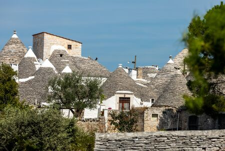 Tradtional white houses in Trulli village. Alberobello, Italy. The style of construction is specific to the Murge area of the Italian region of Apulia (in Italian Puglia). Made of limestone and keystone.