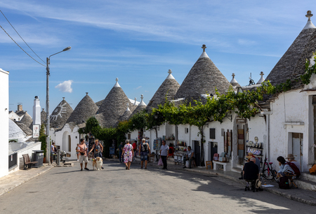 Alberobello, Italy - September 16, 2019: People visit Trulli village in Alberobello, Italy. The style of construction is specific to the Murge area of the Italian region of Apulia (in Italian Puglia). Made of limestone and keystone.