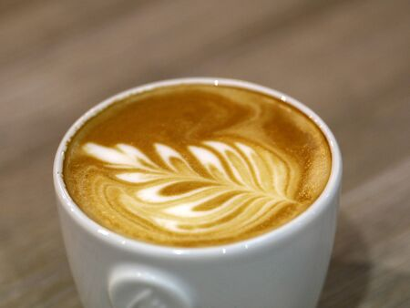 The coffee barista poured milk into the coffee and created a beautiful leaf.