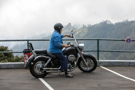 Boca da Encumeada, Madeira, Portugal - April 18, 2018: Motorcyclist in the parking lot on the Boca de Ecumenada pass. Madeira island. Portugal